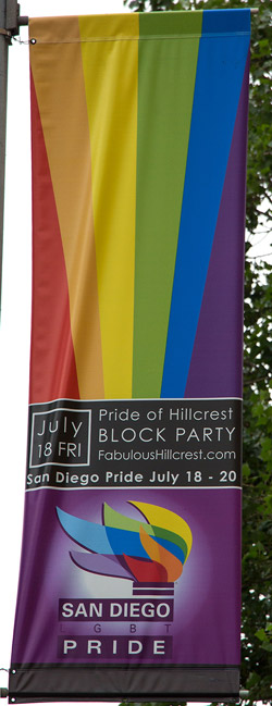 Banner announcing the upcoming pride parade and events on a lamppost in the city